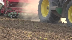 Tractor cultivating and sowing wheat in spring against sunlight. Closeup. 4K Stock Footage