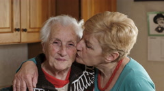 Mature daughter embracing and kissing her old mother, fondness Stock Footage