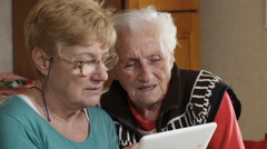 Old grey haired woman learning to use a touchscreen by her niece Stock Footage