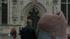 Tilt view of the city hall and women wearing the same scarf walking in Bruges Stock Footage
