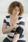 Woman checking  blood pressure by tonometer Stock Photos