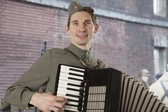 Soviet soldier playing the accordion outdoors - stock photo