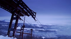Facility ski lift high in the mountains with snow-covered valley and hurried Stock Footage