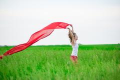 Young lady runing with tissue in green field. Woman with scarf Kuvituskuvat