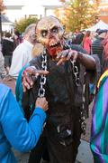 Man In Terrifying Zombie Mask Menaces People At Halloween Festival Stock Photos