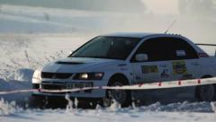 Cool sport pro rally car ride on snow road from close Stock Footage