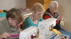 Old woman with grey hair embroidering white her two daughter sew with machine Stock Footage