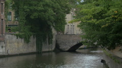 View of a bridge over Dijver Canal and a man clipping bushes in Bruges - stock footage
