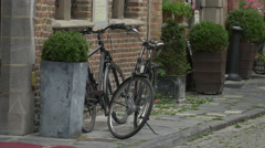 Beautiful view of two parked bikes near an old building in Bruges - stock footage