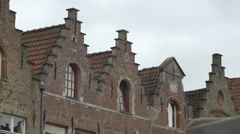 View of old houses with step gable roofs and birds flying in Bruges - stock footage