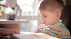 Boy learns to read in the living room - stock footage