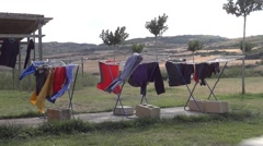 Clothes hanged out to dry on a clothes dryer, a cottage somewhere Stock Footage