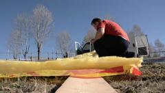 Piece of mineral wool is measured by using a tape, then cut with a cutter 4b Stock Footage