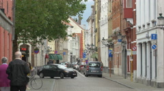 People walking, biking and cars riding on a street with shops in Bruges Stock Footage