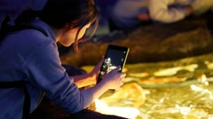 asian girl photographs small fishes on the tablet - stock footage