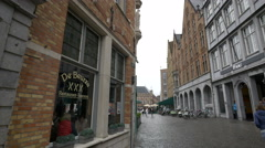 People walking next to De Beurze Restaurant, in the Market Place of Bruges Stock Footage