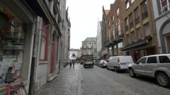 Walking and driving on Philipstockstraat street, next to De Biertempel, Bruges Stock Footage