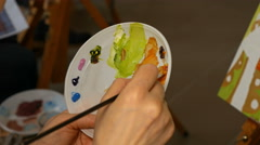 Graphic artist mixing oils color paints in palette - stock footage