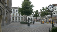 Walking next to the Papageno statue, in front of the City Theatre of Bruges Stock Footage