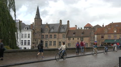 Riding bikes and walking on Dijver canal's waterfront in Bruges Stock Footage
