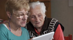 grey haired granma looking pictures of her nieces on a tablet - stock footage