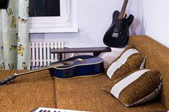 Synthesizer lying on a brown sofa in the house - stock photo