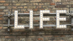 'Life letters' with bulbs on a brick wall in Bruges Stock Footage