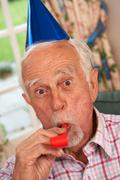Senior Man Celebrating With Party Hat And Blower - stock photo