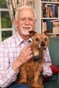 Senior Man At Home With Pet Dog - stock photo