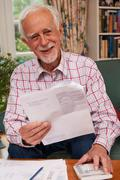 Senior Man Going Through Finances Looking Happy And Secure Stock Photos