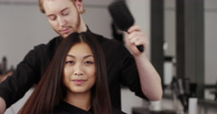 A hairdresser styling a young woman's hair. Shot on RED Epic. Stock Footage