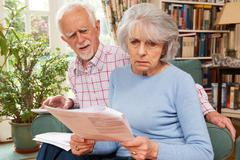 Senior Couple Going Through Finances Looking Worried - stock photo