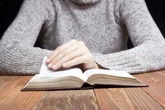 Closeup woman hand  holding pocket book to read Stock Photos