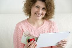 woman with tablet pc computer and credit card, money at home - stock photo