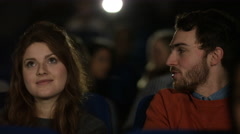 4K Cinema audience watching a movie with focus on happy young dating couple - stock footage