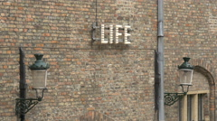 Life letters on a brick wall in the Belfy of Bruges's interior courtyard Stock Footage