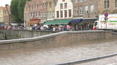 Many tourists with umbrellas walking along Dijver Canal in Bruges Stock Footage