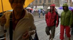 People with umbrellas walking on Rozenhoedkaai in Bruges Stock Footage