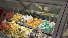 Sales assistant scooping out frozen gelato from a display cabinet, rome Stock Footage