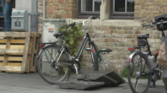 Two bikes parked near a brick building in Bruges Stock Footage