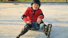 Injured young boy falling off skate, sitting on the floor Stock Footage