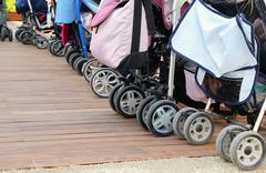 many strollers for toddlers parked on the parquet floor of wood - stock photo