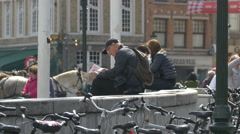 Man reading the newspaper in Market Square, Bruges Stock Footage