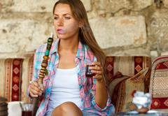 Woman smoking a hookah and drinking tea in a cafe, Istanbul, Turkey Stock Photos