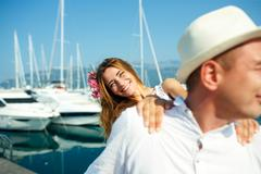 Attractive young couple walking alongside the marina - wedding concept - stock photo