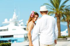 Attractive young couple walking alongside the marina with moored boats on a l - stock photo