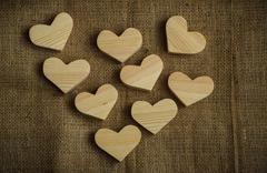 Wooden hearts on sackcloth background - stock photo