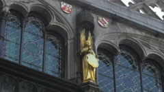 View of an angel statue and coat of arms on a church in Burg Square, Bruges Stock Footage