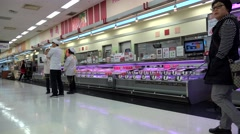 Shoppers in a Korean grocery supermarket. Section of meat. Stock Footage