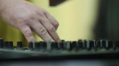 Hands of a DJ on mixing sound board, at a party Stock Footage